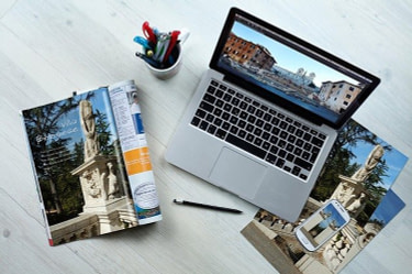 One-Of-The-First-Ways-To-Earn- Money-Laptop-computer-with-a -mobile-phone-a travel-brochure-and-apen